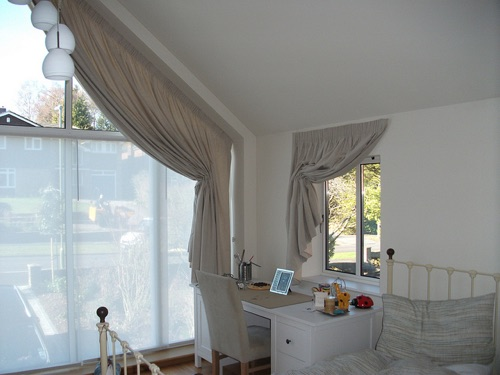 An architect designed, full wall, shaped window is difficult to curtain, but here one in a bedroom is dressed with a large Italian strung curtain and a Silent Gliss semi sheer  roller blind.