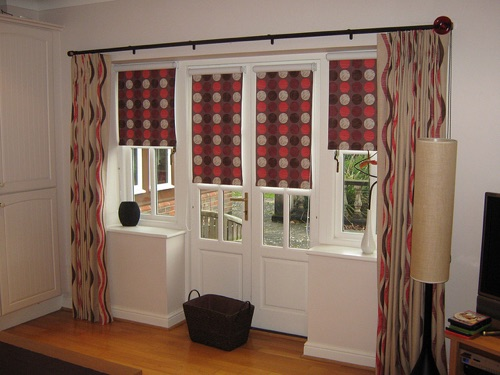Dramatic co-ordinating roman blinds and curtains at these French doors and windows, show how simple drops of fabric can give enormous impact to a window.